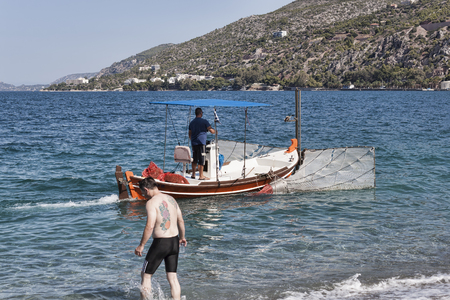 LOUTRAKI, GREECE - JULY 3, 2018: The sea on the beach in Loutraki is very clean, despite this, every day several times a boat sailing, which cleans the trash