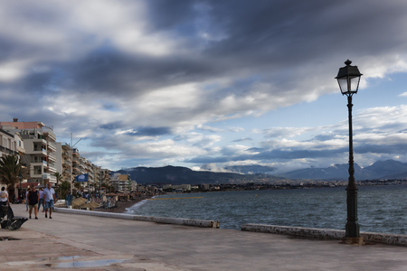 LOUTRAKI, GREECE - JUNE 27, 2018: The embankment of Loutraki on a cloudy summer day. Even in bad weather there are many tourists