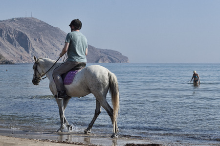 GEORGIOUPOLIS, CRETE, GREECE - JULY 31, 2013: Unidentified rider on a horse on the beach. Horseback riding in Crete one of the favorite pastimes of vacationers Editorial