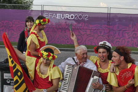 DONETSK, UKRAINE - JUNE 27, 2012: Fans of the Spanish national team sing along with the accordionist from Ukraine before the semifinal match of EURO 2012 in Donetsk