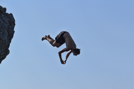 ALUPKA, CRIMEA, UKRAINE - AUGUST 23, 2012: An unidentified young man in flight after jumping from a cliff to the sea. Extreme jumps from the rocks are popular in the Crimea