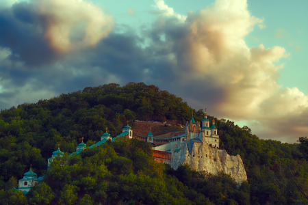 Church of St. Nicholas on the Cretaceous mountain in Sviatohirsk in the evening. Over the mountain is the dramatic sky