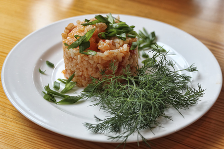 Rice in Hungarian style with paprika on a white plate with green onions and dill