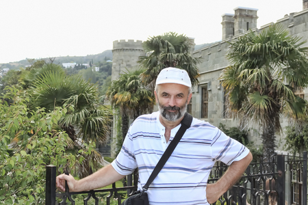 A middle-aged man with a beard and a baseball cap in the courtyard of the Vorontsov Palace. Ukraine, Crimea, Alupka