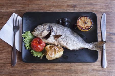 Dorado fish on a black plate. Served with a lettuce leaf on which baked peppers and a tomato, there are also a few olives and a slightly baked lemon