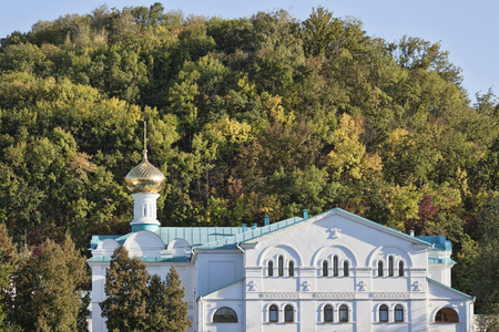 Buildings Sviatohirsk Lavra against the background of a small hill, covered with lush vegetation. Autumn is approaching Stock Photo