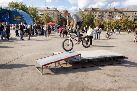 SLOVIANSK, UKRAINE - SEPTEMBER 11, 2011: Unidentified byker performs a trick on a bicycle at the city festival in Sloviansk on September, 2011