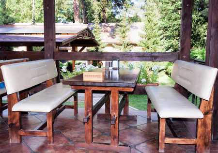 Reserved table in the open porch of a forest restaurant
