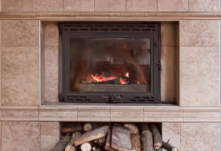 Fireplace with a closed glass door. Below are the firewood prepared for tossing.