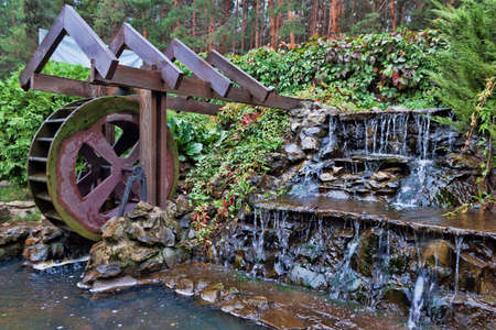 A small watermill next to a small artificial waterfall in the forest 写真素材