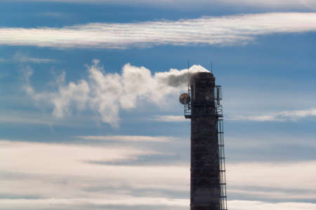 Chimney, towering against the blue sky with clouds. Smoke billows from the chimney.