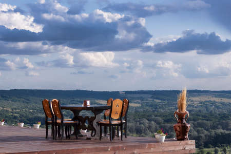 A table and several chairs on a pedestal, which rises on the mountain. Against a breathtaking sky and landscape below 写真素材