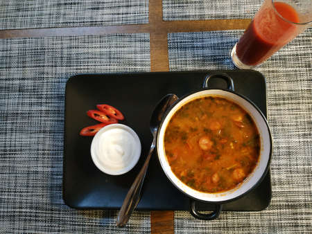 Hungarian spicy soup. Served on a black porcelain tray in a deep bowl. On a tray is a small bowl with sour cream and pieces of red pepper. Nearby is a glass of juice 写真素材