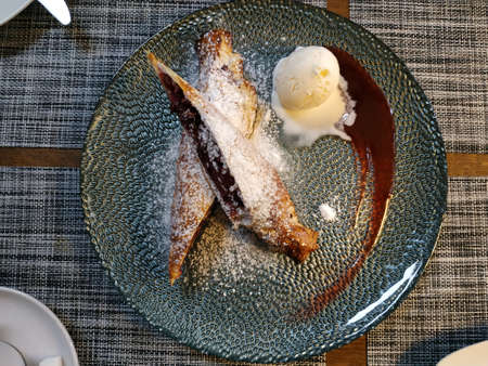 Cherry strudel sprinkled with powdered sugar, next to a scoop of ice cream and spilled jam