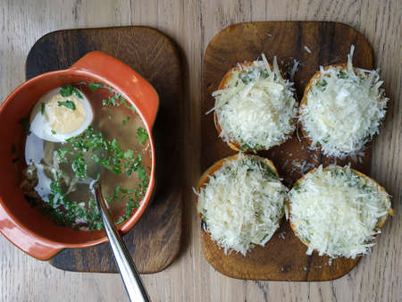 CHICKEN BROTH. Chicken stock, chicken, chicken eggs, parsley. Nearby croutons sprinkled with parmesan. Served on wooden planks 写真素材