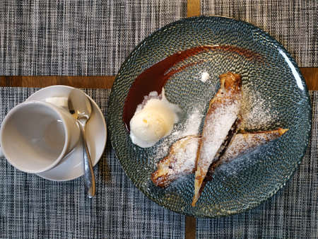 Cherry strudel sprinkled with powdered sugar, next to a scoop of ice cream and spilled jam. Near cup for tea