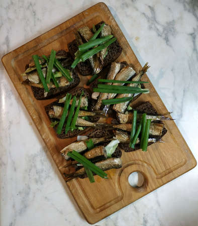 Sandwiches with sprats on brown bread, decorated with green onions. Served on a wooden board for cutting vegetables 写真素材