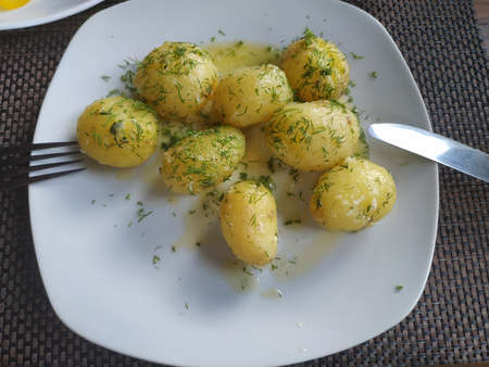 On a white plate is a freshly cooked young potato, sprinkled with oil and sprinkled with dill. 写真素材