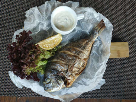 Baked dorado on parchment paper with lettuce, a slice of lemon and a bowl of white sauce