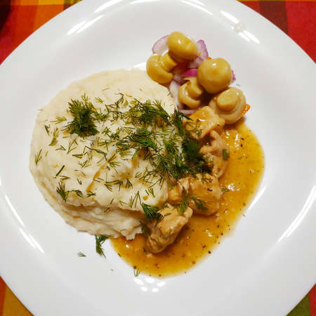 On a large white plate, mashed potatoes sprinkled with green dill, next to pieces of stewed turkey in gravy and pickled mushrooms with onions
