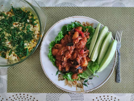 Vegetable stew, laid out on a leaf of lettuce, with sliced pieces of cucumber. Next to a dish with baked colored cabbage sprinkled with herbs 写真素材