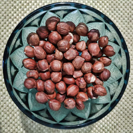 In a decorative glass vase a handful of hazelnuts. View from above