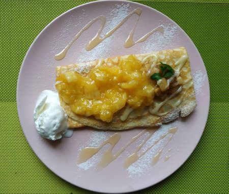 Pancake with orange marmalade and ice cream. Garnished with icing sugar and jam