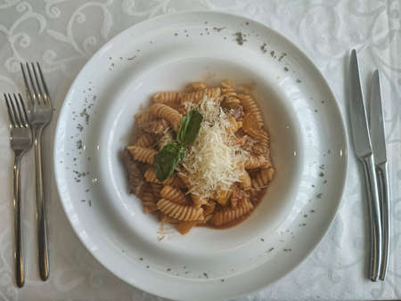 Fusilli with veal. In a large deep plate on a table covered with a white tablecloth, next to cutlery 写真素材