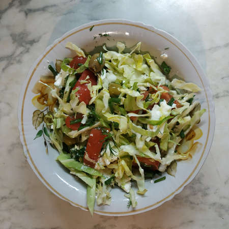 Vegetable salad: cabbage, tomatoes, olives, onions and more in a deep bowl. View from above