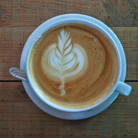 A cup of cappuccino with sophisticated foam patterns on a table of roughly treated boards. Top view