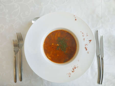 Spicy tomato soup with meat mix. In a plate with wide fields, cutlery on the sides