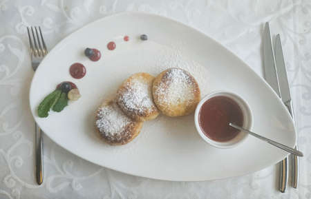 Syrnik with jam. In a plate of a triangular shape, cutlery on the sides