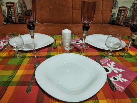 Served New Year's table. Large plates, glasses for cognac and tall glasses for champagne on a bright checkered tablecloth 写真素材