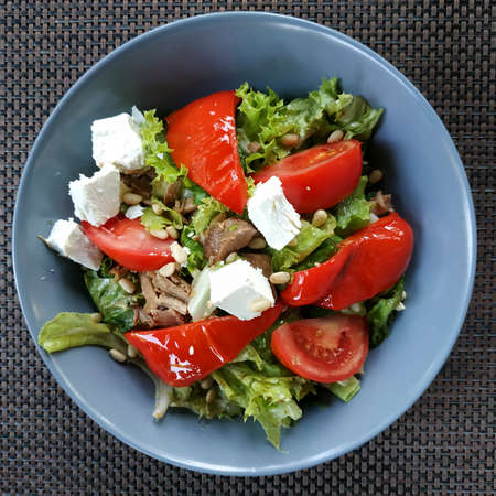 Vegetable salad with tomatoes, baked bell pepper, cheese and pieces of turkey meat, decorated with lettuce leaves and sprinkled with cumin
