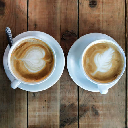 Two cups of cappuccino with intricate foam patterns on a table made of roughly treated boards. Top view