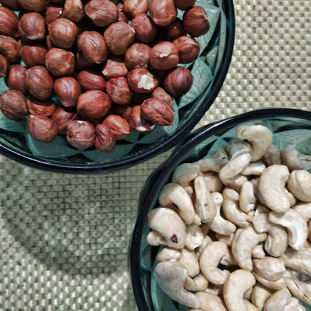 In decorative glass vases with handfuls of cashews and hazelnuts. View from above 写真素材
