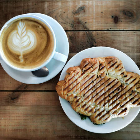 A cup of cappuccino with intricate patterns of foam and croissants stuffed on a table of roughly treated boards. View from above