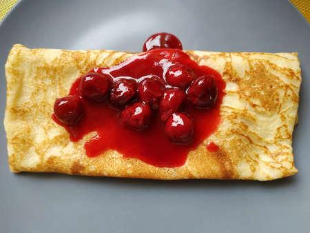 Pancake with cherry jam. On a big gray plate