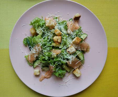 CAESAR WITH SALMON. Salad mix, fresh cucumber, slightly salted salmon, Parmesan cheese, crackers, Caesar sauce