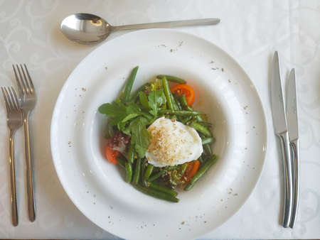 Salad of green beans with poached egg and orange cream sauce. In a large deep plate on a table covered with a white tablecloth, next to cutlery 写真素材