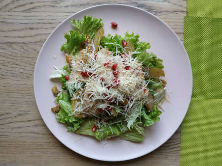 Nice salad. Salad mix with turkey fillet, with pear and pomegranate seeds, sprinkled with parmesan cheese