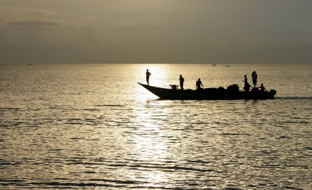 Silhouette of Lombok fishermen back from the ocean photo