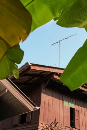 Wooden house with Old-style antenna on the roof  Editorial