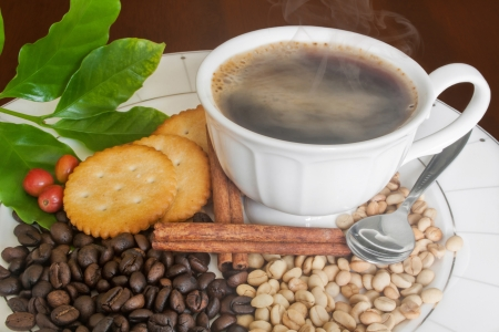 Smoking hot coffee, Black beans, White beans, Ripe coffee beans , coffee leafs,Cinnamon and Cracker on Plate