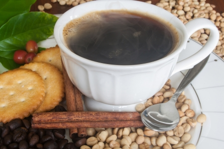 Coffee cup, beans, cinnamon and cracker Stock Photo