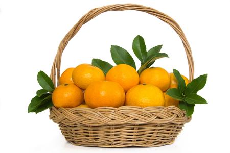 A basketful of mandarin oranges and leafs on white
