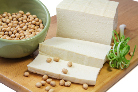 Tofu and Soybeans on a chopping block with green onion  Stock Photo