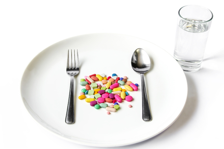 Drugs medicine on a dish with fork  spoon and a water glass on white background.