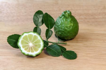 Fresh Kaffir lime and leaf on wood background.
