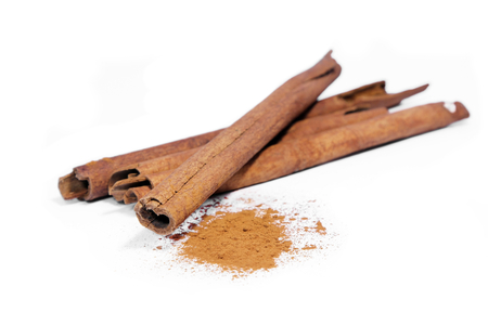 Cinnamon sticks and powder on white background.
